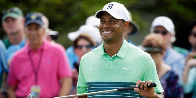 Tiger Woods smiles as waits to putt during a practice round for the Masters golf tournament Wednesday, April 8, 2015, in Augu