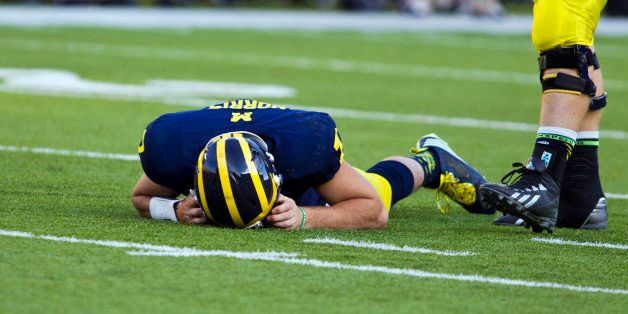 In this Sept. 27, 2014, photo, Michigan quarterback Shane Morris lays on the field after taking a hit in the fourth quarter o