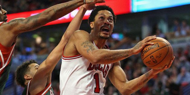 CHICAGO, IL - APRIL 20:  Derrick Rose #1 of the Chicago Bulls drives to the basket pagainst O.J. Mayo #00 and Michael Carter-