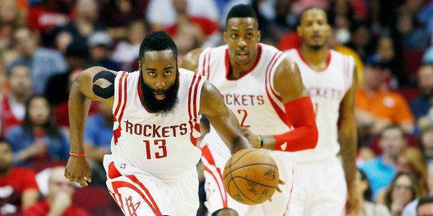 HOUSTON, TX - APRIL 15:   James Harden #13 of the Houston Rockets takes the baskeball upcourt as Dwight Howard #12 and Trevor