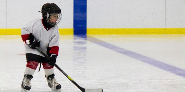 Little boy playing ice hockey