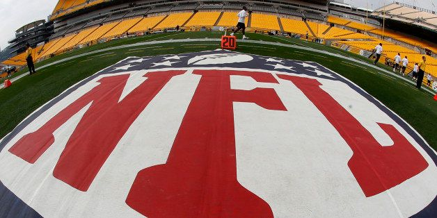 In this image made with a fisheye lens, the NFL logo is displayed on the sideline of Heinz Field as the Tennessee Titans warm