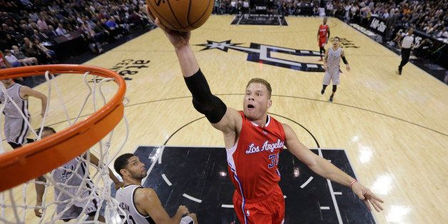 Los Angeles Clippers' Blake Griffin scores over San Antonio Spurs' Tim Duncan (21) during the first half of an NBA basket