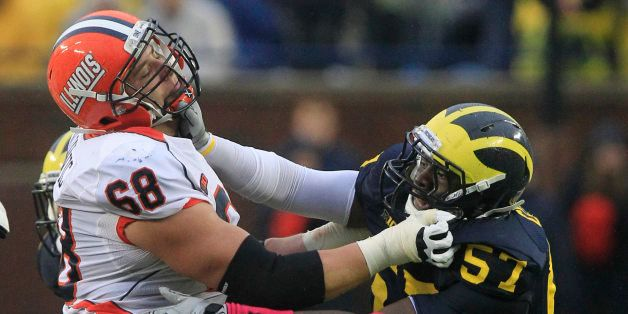Michigan defensive end Frank Clark (57) goes up against Illinois offensive linesman Simon Cvijanovic (68) during the second h