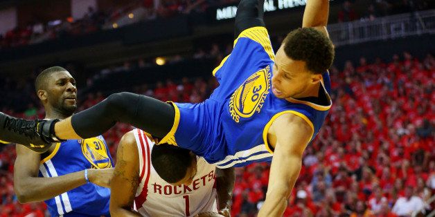 HOUSTON, TX - MAY 25:  Stephen Curry #30 of the Golden State Warriors falls over Trevor Ariza #1 of the Houston Rockets on hi