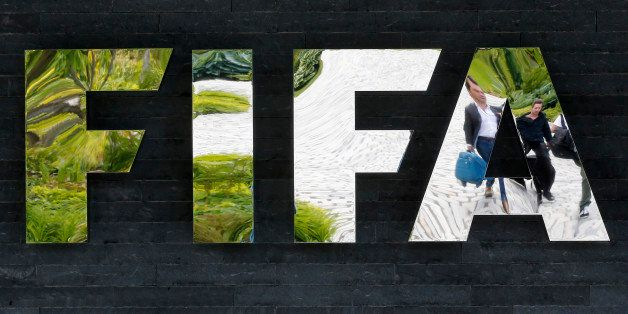 Two persons are reflected in the FIFA logo at the FIFA headquarters in Zurich, Switzerland, Wednesday, May 27, 2015. Swiss pr