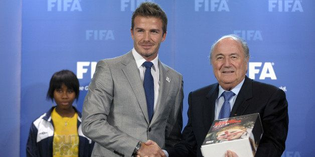 FIFA president Sepp Blatter (R) poses after receiving the bid books for 2018 and 2022 FIFA World Cups from former England foo