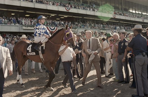 Trainer Jack Van Berg accompanies his horse Alysheba and jockey Chris McCarron after failing in their bid for the Triple Crow