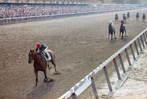 Easy Goer, piloted by Pat Day, left, moves to an eight-length finish ahead of Sunday Silence, second left, to win the Belmont