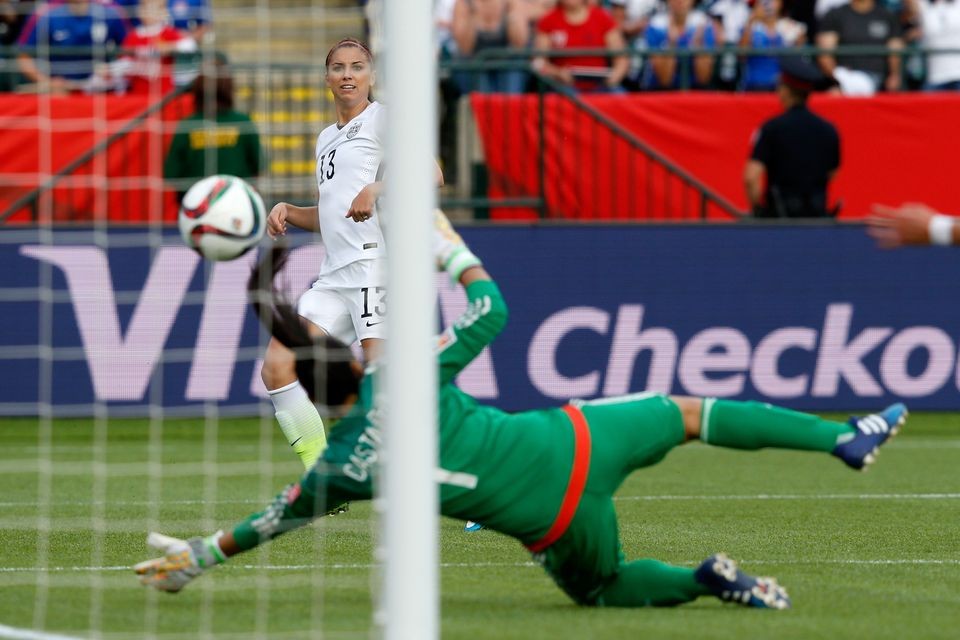 EDMONTON, AB - JUNE 22:  Alex Morgan #13 of the United States scores her first goal against goalkeeper Stefany Castano #1 of