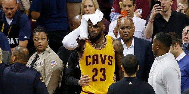 Cleveland Cavaliers forward LeBron James (23) holds a towel to his head after being knocked into the fans during the first ha