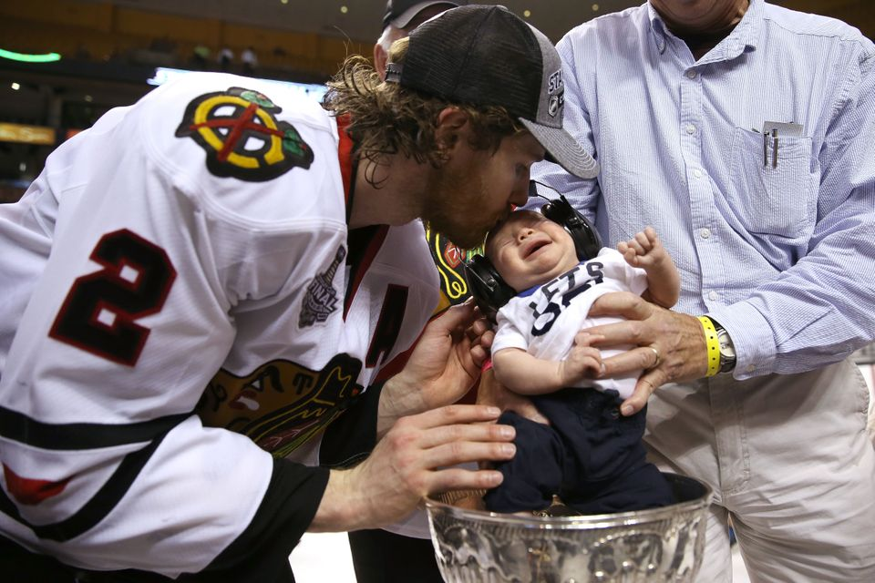 Duncan Keith #2 of the Chicago Blackhawks celebrates a 2-1 victory over the Boston Bruins with his son following Game Six of