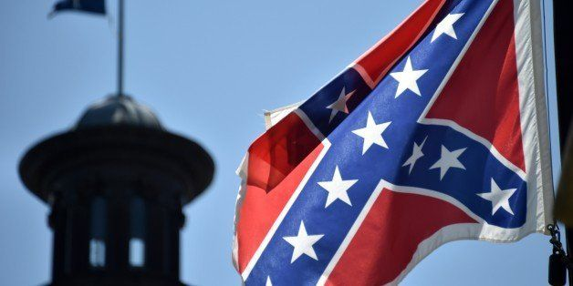 The South Carolina and American flags flying at half-staff behind the Confederate flag erected in front of the State Congress
