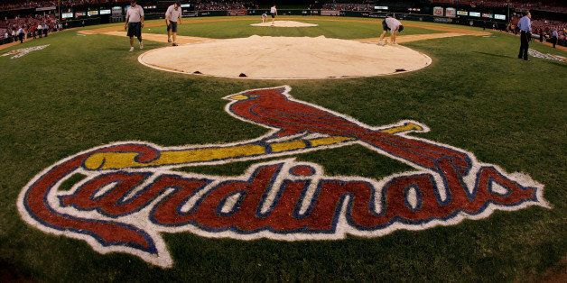 ST. LOUIS - OCTOBER 19:  Stadium workers cover home plate with a tarp as security keeps a close eye on fans remaining in the