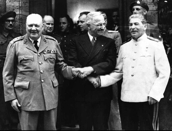 President Harry Truman shakes hand with Soviet General Secretary Josef Stalin (right) and British Prime Minister Winston Chur
