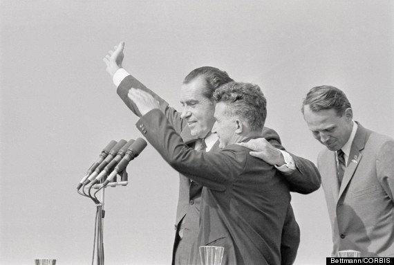 Nixon puts his arm around the shoulder of President Nicolae Ceausescu of the Socialist Republic of Romania as the two men wav