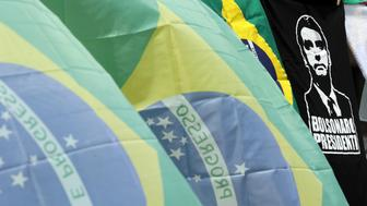 National flags and shirts with the image of Brazil's presidential candidate Jair Bolsonaro are seen for sale in front of Pacaembu Stadium in Sao Paulo, Brazil September 29, 2018. Picture taken September 29, 2018. REUTERS/Paulo Whitaker