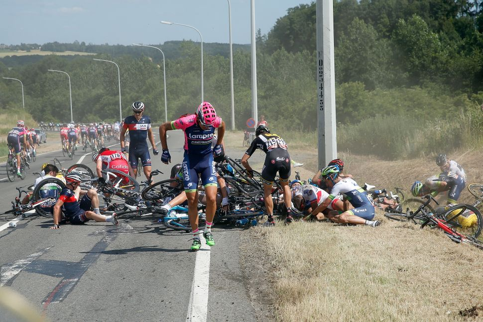 Riders collect themselves after a crash with 65km left to race in stage three of the 2015 Tour de France from Anvers to Huy o