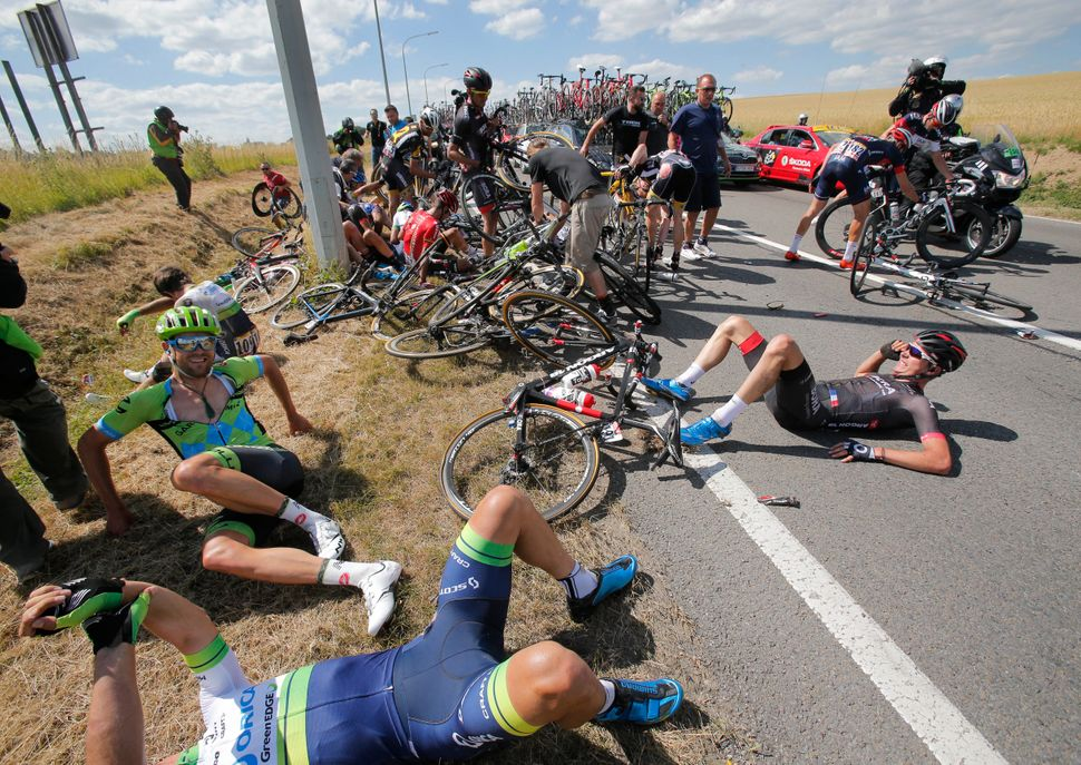 Scores of riders lie on the road after crashing during the third stage of the Tour de France cycling race over 159.5 kilomete