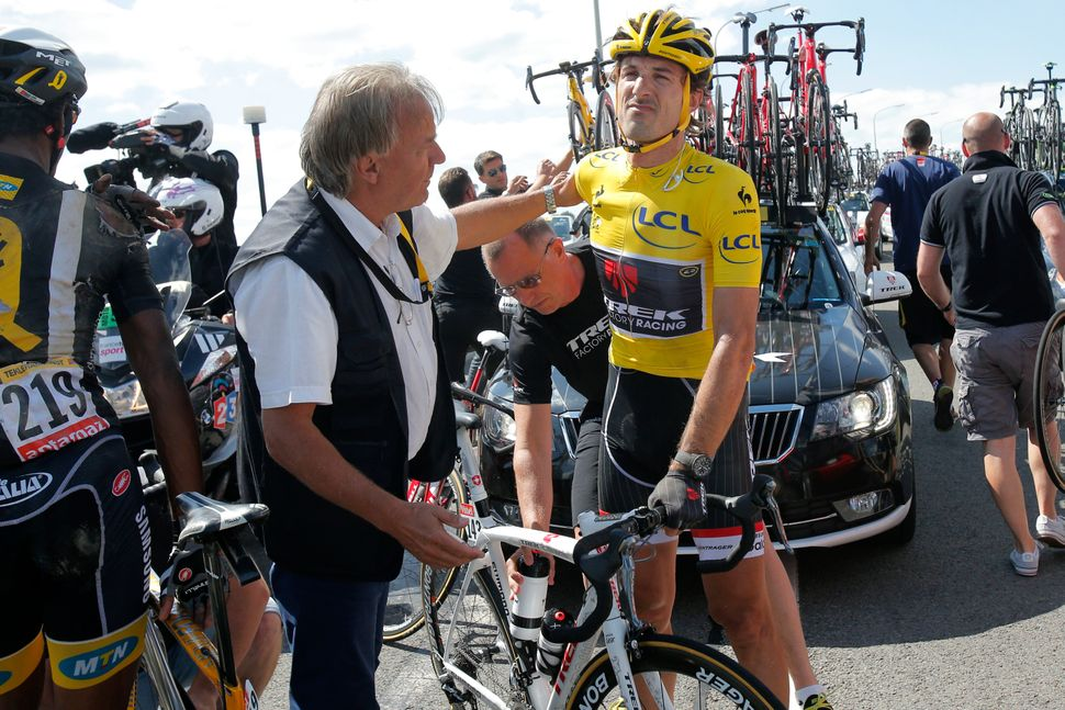 Switzerland's Fabian Cancellara, wearing the overall leader's yellow jersey, gets back on his bicycle after crashing with sev