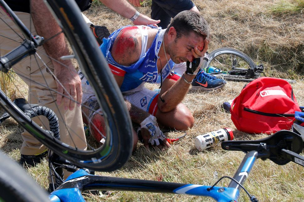 William Bonnet of France holds his head after crashing with scores of other riders during the third stage of the Tour de Fran