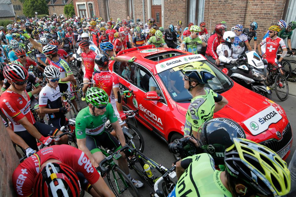 Riders wait for a restart after the race was neutralized following a crash involving scores of riders during the third stage