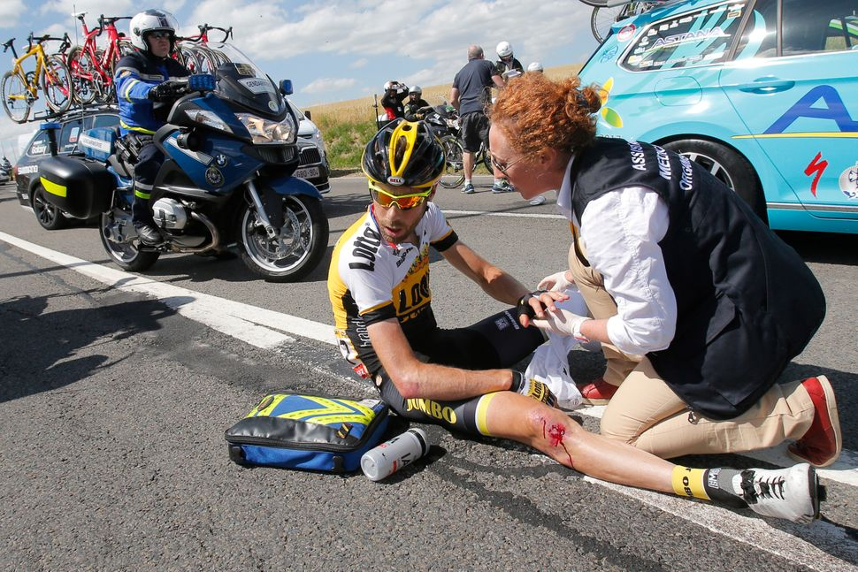 Laurens ten Dam of the Netherlands is treated for injuries after crashing with several of other riders during the third stage