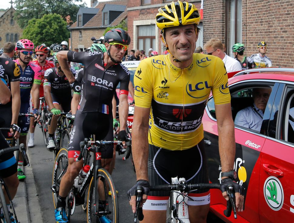 Switzerland's Fabian Cancellara, wearing the overall leader's yellow jersey, grimaces after catching up with the pack followi