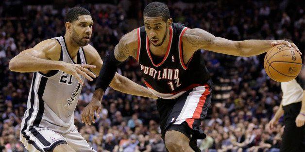 Portland Trail Blazers' LaMarcus Aldridge (12) drives around San Antonio Spurs' Tim Duncan (21) during the second half on an