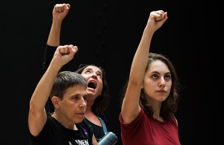 Detained protesters gesture at the Senate Hart building during a rally against Supreme Court nominee Brett Kavanaugh on Capit