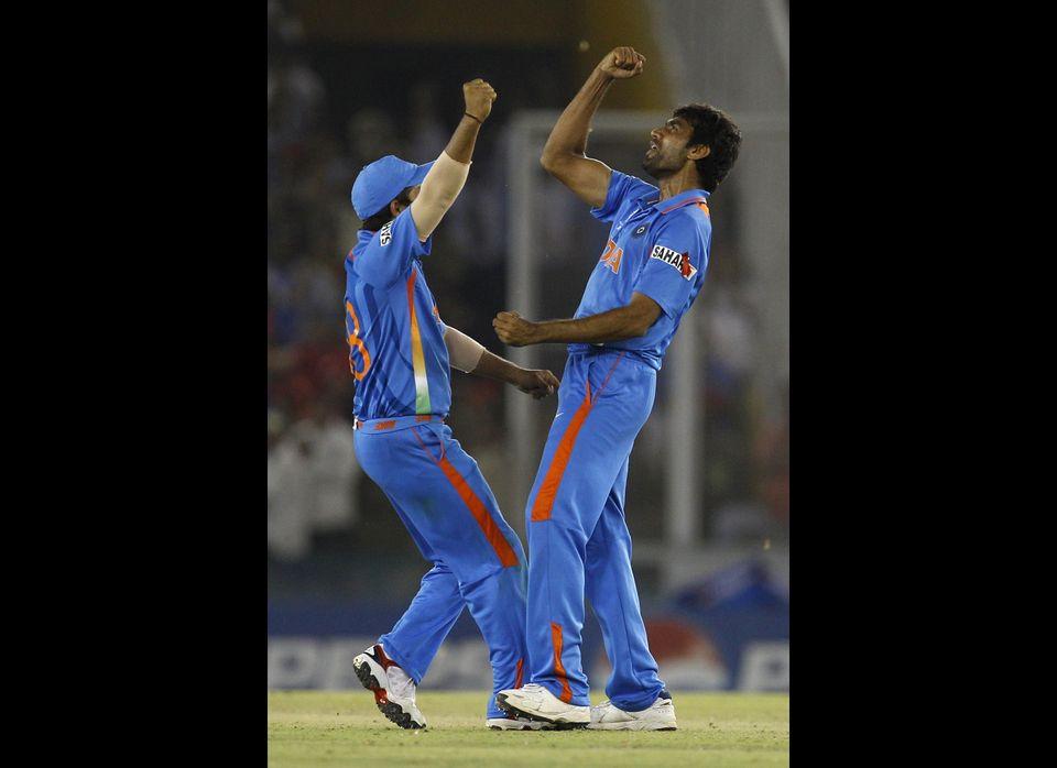 India's Munaf Patel, right, celebrates with Suresh Raina the dismissal of Pakistan's Abdul Razzaq, not seen, during the Crick
