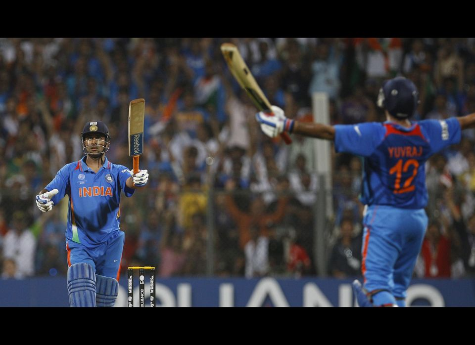 India's captain Mahendra Singh Dhoni, left, watches his winning shot as batting partner Yuvraj Singh runs to him to celebrate