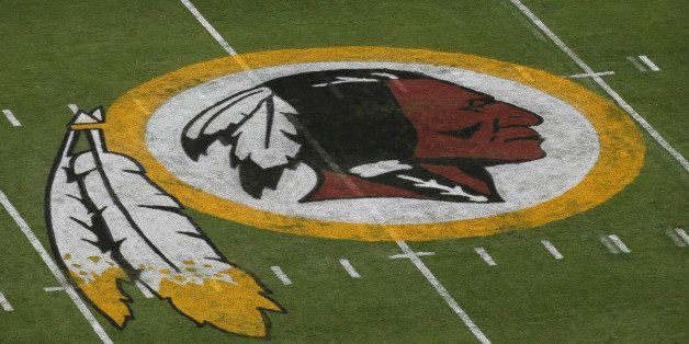In this photo taken Aug. 7, 2014, the Washington Redskins logo is seen on the field before an NFL football preseason game aga