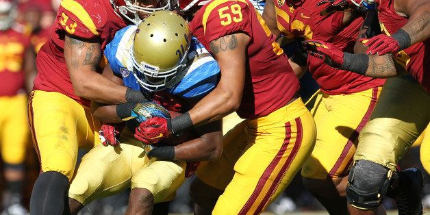 LOS ANGELES, CA - NOVEMBER 28:  Paul Perkins #24 of the UCLA Bruins is tackled by the USC Trojan defense during a 40-21 Troja