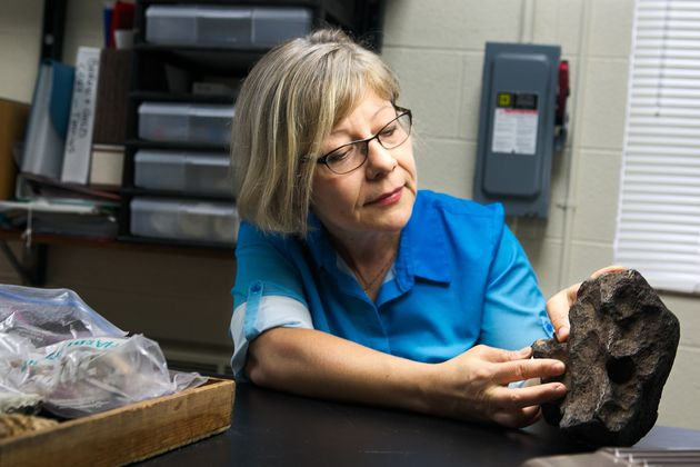 CMU geology faculty member Mona Sirbescu holds the 22.5 pound meteorite used as a doorstop for