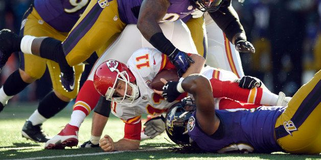 Kansas City Chiefs quarterback Alex Smith (11) gets tangled with Baltimore Ravens as he tries to protect the ball in the firs