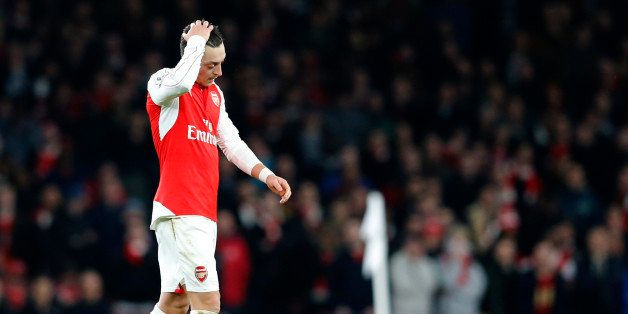Arsenal's Mesut Ozil puts his hand to his head as he waits for a free kick to be taken during the English Premier League socc