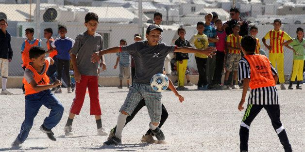 Syrian refugee children play soccer as others watch at the Zaatari refugee camp in Mafraq near the Syrian border in Jordan, S