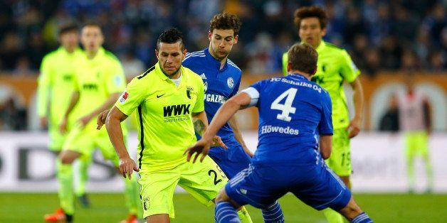 Augsburg's Raul Bobadilla, left, Schalke's Leon Goretzka, background, and Schalke's Benedikt Hoewedes challenge for the ball