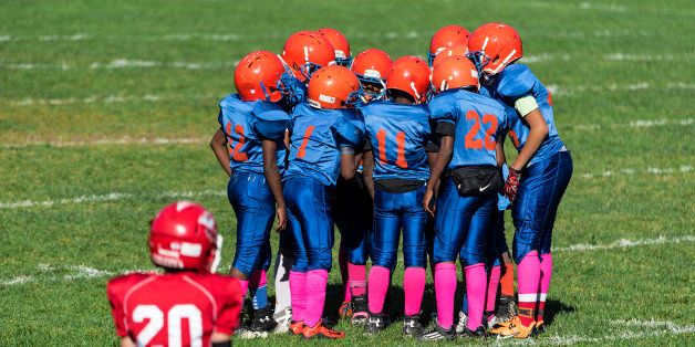 UNITED STATES - 2015/10/11: Young boys in the huddle during a Pop Warner football game. (Photo by John Greim/LightRocket via