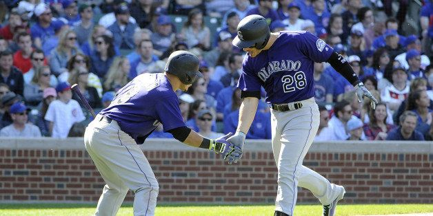 Colorado Rockies' Nolan Arenado (28) is greeted by teammate Gerardo Parra (8) after hitting a solo home run against the Chica