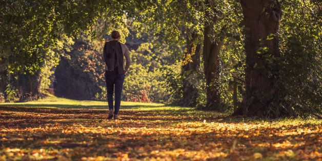 Solitary woman wanders contemplatively through a autumnal tree lined pathway with her jacket slung over her shoulder and the