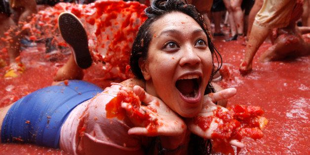 """A woman lays on a puddle of tomato juice during the annual """"tomatina"""" tomato fight fiesta in the village of"""