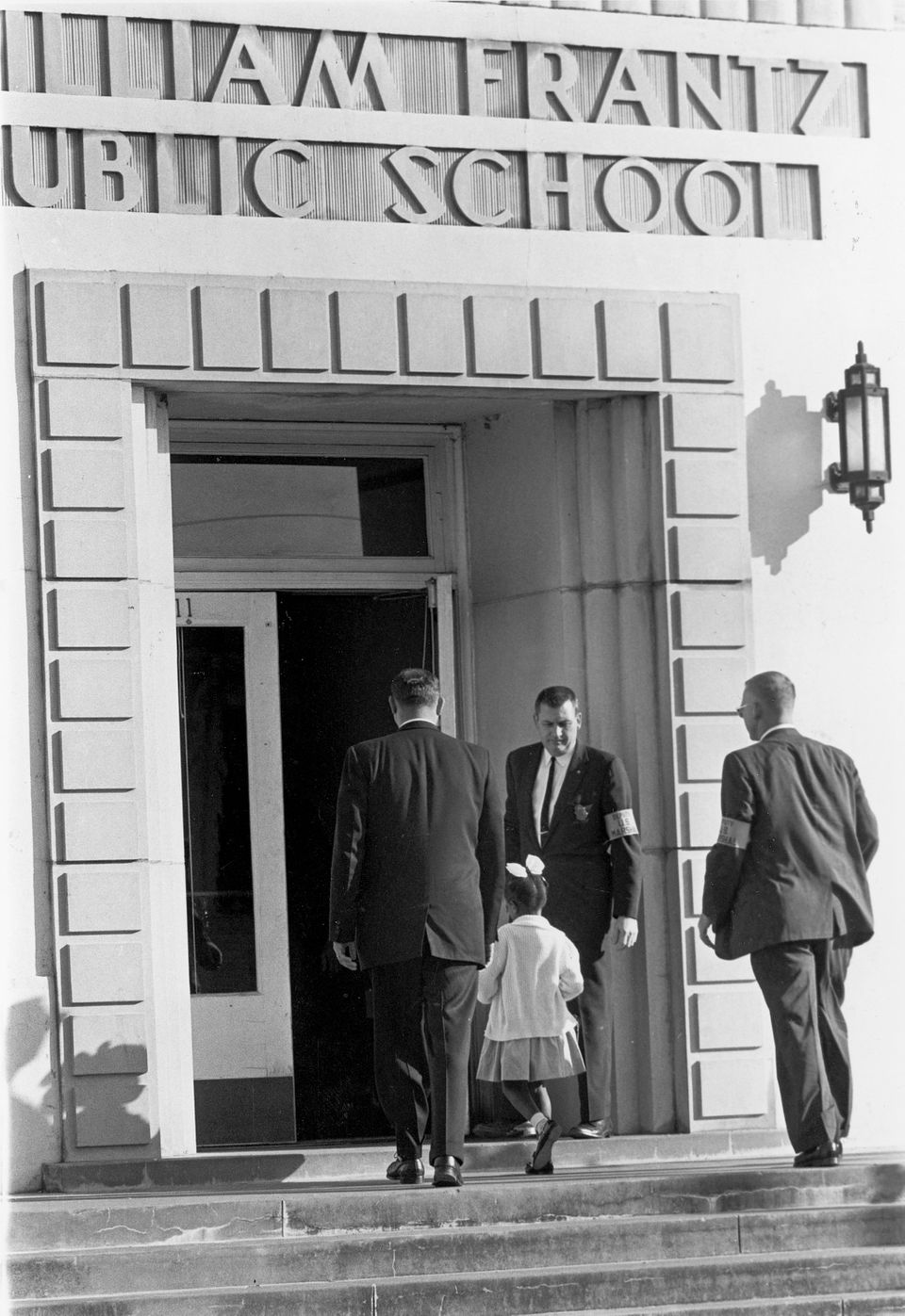 Guarded by three Deputy U.S. Marshals,, young Ruby Bridges enters newly integrated William Frantz school in New Orleans, La.