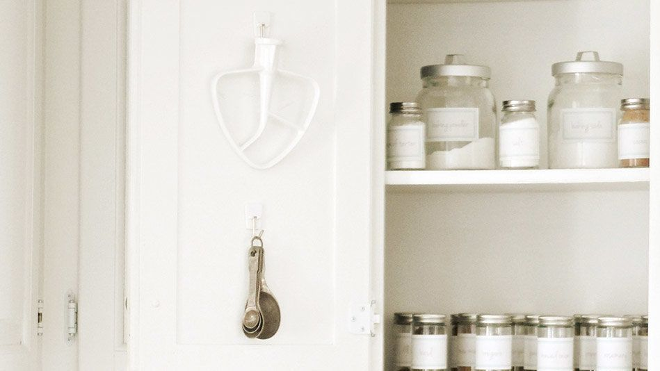 Stick a few adhesive hooks to the inside of each one to hang measuring cups, oven mitts or stand-mixer attachments, like <a h