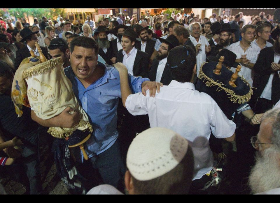 Jews dance with the Torah scrolls during the Simchat Torah celebration in the coastal city of Netanya, north of Tel Aviv on S