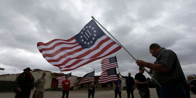 Anti-Muslim protestor gather across the street from a mosque in Richardson, Texas, Dec. 12, 2015. (AP Photo/LM Otero)