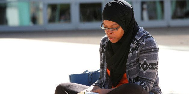Tauhdedah El-Saadiq, of Louisville, reads a Koran while waiting for the ticket office to open for tickets to boxing legend Mu