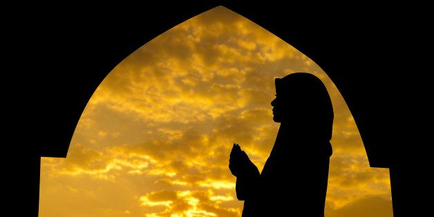 Silhouette of Female Muslim praying in mosque during sunset time