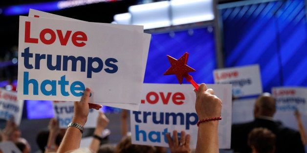 "Delegates wave ""Love trumps hate"" signs towards the podium during the first session at the Democratic National Convention in"